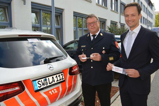 """Landrat Florian Töpper und Kreisbrandrat Holger Strunk präsentieren den neuen Aufkleber """"Rettungsgasse bilden"""", der nun auch auf sämtlichen Dienstfahrzeugen des Landratsamtes zu sehen ist. (Foto: LRA SW, Uta Baumann)"""