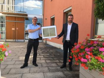Das Foto zeigt mit einer Kopie der historischen Urkunde von 1921 von links Frank Schneider (Kommunalmanagement der Bayernwerk Netz GmbH) und Bürgermeister Stefan Rottmann.
