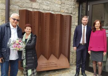 Das Foto zeigt von links vor dem Denkmal in Schonungen: Naftali Fürst, Lebensgefährtin Tova Wagman, Bürgermeister Stefan Rottmann und Schulleiterin Christine Seuffert.